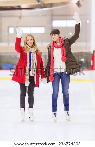 people, women, friendship, sport and leisure concept - two happy girls friends waving hands on skating rink - stock photo