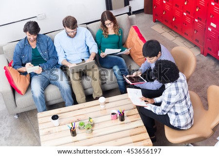 People working office sitting sofa using phone tablet computer diverse mix race group businesspeople casual wear top angle view - stock photo