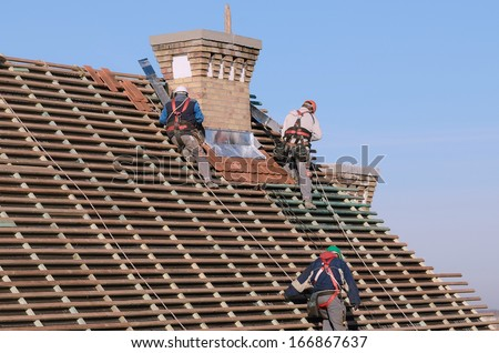 People working on the new roof - stock photo