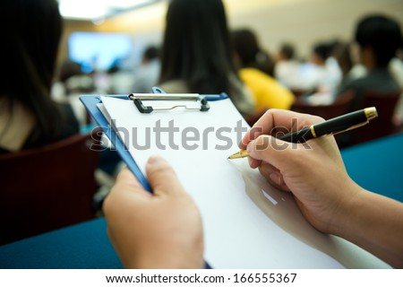 people writing on the document in a business seminar. - stock photo