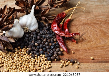 Pepper and dried Chilli on wooden board - stock photo
