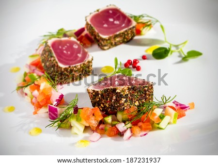 Pepper coated and lightly seared raw tuna chunks served with finely chopped vegetable salad and sprinkled with sea salt - stock photo