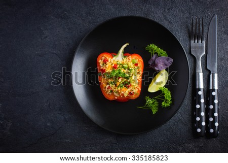 pepper staffed with couscous and vegetables on black plate, top view, copy space - stock photo