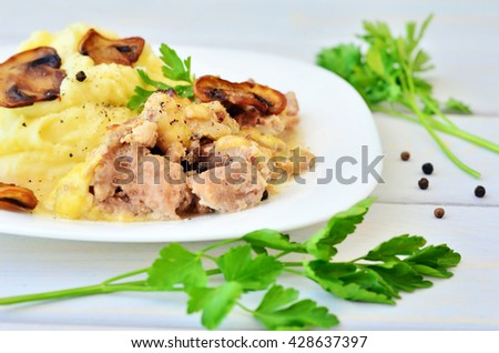 Pepper, twigs of parsley on a wooden table next to a white plate with mashed potatoes, meat and mushrooms - stock photo