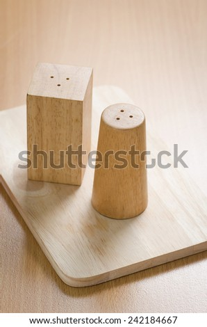 pepperbox  and salt cellar on wooden table background - stock photo