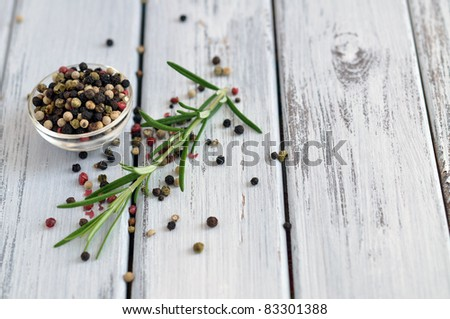 Peppercorn mix in a glass bowl and fresh rosemary on an old white table - stock photo