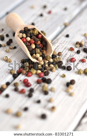 Peppercorn mix in a wooden scoop on an old white table - stock photo