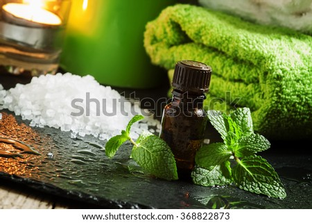Peppermint essential oil in a Spa concept with towel, sea salt, aromatic candles on a dark wet background, selective focus - stock photo