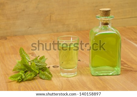 Peppermint plant, liqueur bottle and shot on wooden background - stock photo