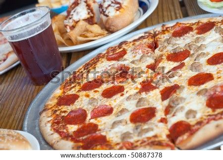 Pepperoni and Sausage Pizza with Beer - stock photo