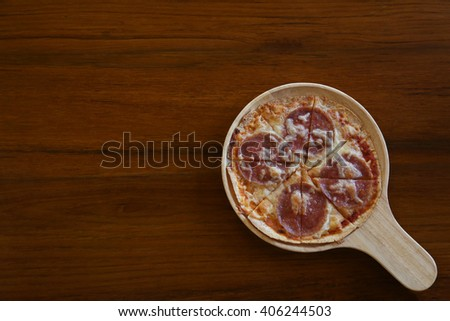Pepperoni pizza on wooden table background. Top view with copy space - stock photo