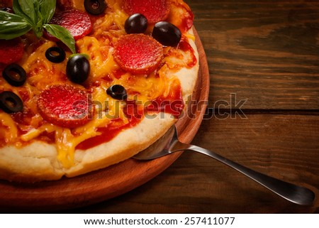 Pepperoni pizza on wooden table top view - stock photo