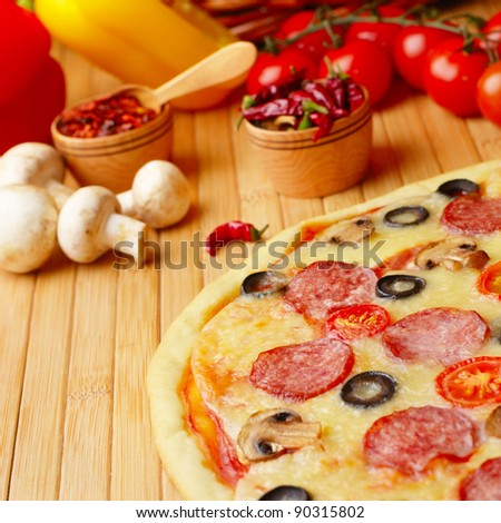 Pepperoni pizza with cherry and mushrooms on the bamboo kitchen table - stock photo