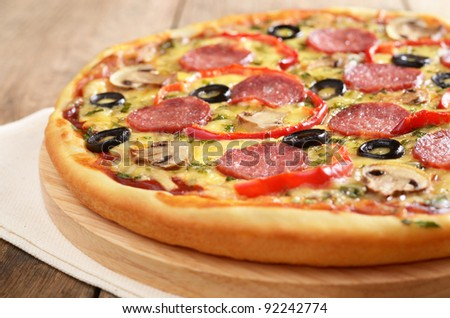 Pepperoni pizza with mushrooms on the wooden board closeup - stock photo