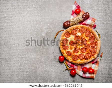 Pepperoni pizza with salami and tomatoes. On the stone table. Free space for text . Top view - stock photo