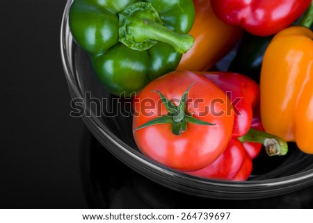 Peppers and tomatoes in glass bowl on black - stock photo