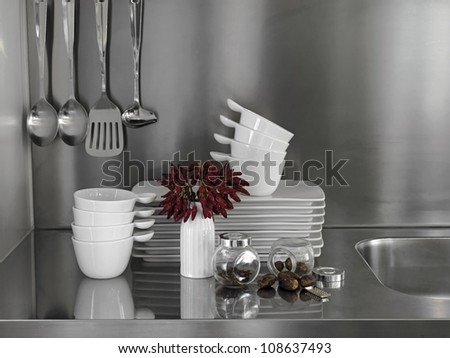 peppers and white dishes on the steel surface in the kitchen - stock photo