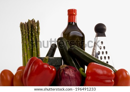 Peppers, asparagus, onion, a bottle and cheese grater grouped together. - stock photo