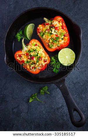peppers staffed with couscous and vegetables on cast iron pan, top view - stock photo