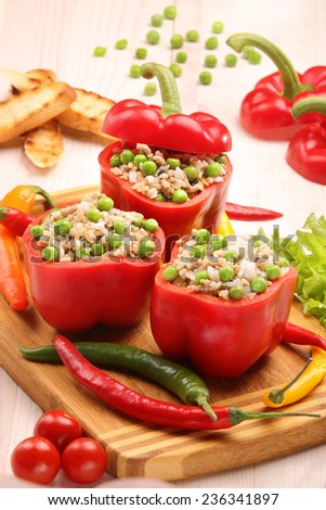 Peppers stuffed with meat rice and vegetables on cutting board - stock photo