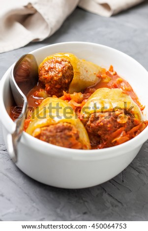 peppers stuffed with tomato sauce in a white dish for roasting on a concrete background - stock photo