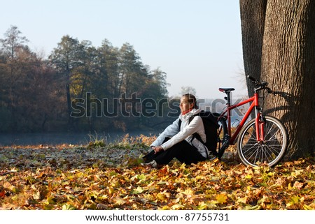 Peppy woman cyclist with bike sits among fallen leaves autumn morning in nature illuminated by the rays of the rising sun - stock photo