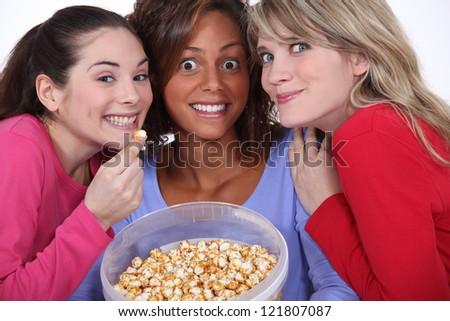 Peppy women eating popcorn - stock photo
