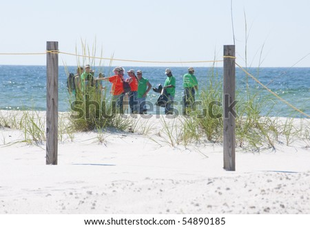 PERDIDO KEY, FL - JUNE 9: BP oil spill workers clean the beaches on June 9, 2010 as oil threatens the pristine Gulf Shores National seashore near Pensacola, FL. - stock photo