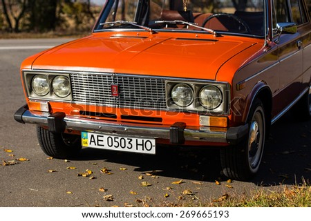 PERESHCHEPINO, UKRAINE - OCTOBER 12, 2014: Zhiguli VAZ 2106 original orange, released in the USSR in 70's. Car parked on the side of the road in the middle of sunny day without cars nearby - stock photo
