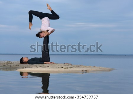 Perfect acro yoga. Beautiful young couple pair is balancing doing acro yoga. Pair yoga concept. Yoga flexibility outdoor class workout. Healthy yoga lifestyle - stock photo