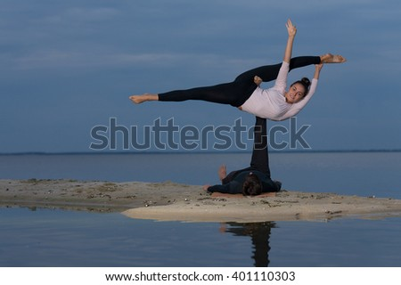 Perfect acroyoga. Beautiful young couple is balancing doing acro-yoga. Pair yoga concept. Yoga flexibility outdoor class workout - stock photo