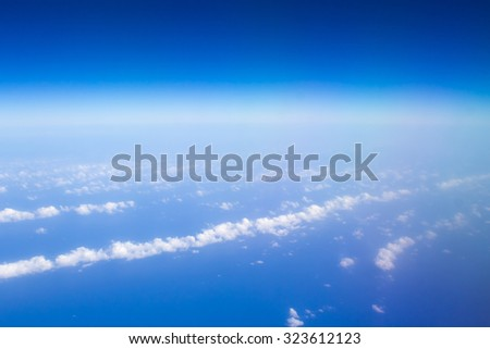 Perfect airplane view of atlantinc ocean with a few fluffy clouds and clear blue sky - stock photo