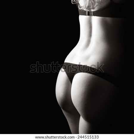 Perfect back of a young woman in black bra and panties in front of dark studio background, monochrome closeup photo with copy space on the left side of the image - stock photo