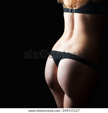 Perfect back of a young woman in black bra and panties in front of dark studio background, closeup photo with copy space on the left side of the image - stock photo