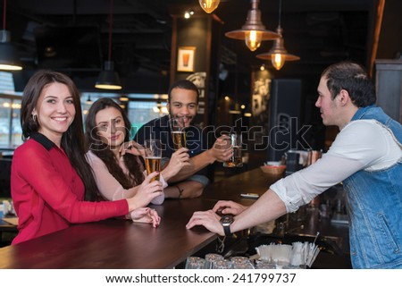 Perfect beer party. Portrait of young beautiful girl is standing in a pub with glass of beer and smiling. Her friends are standing next to her and talking with barman - stock photo