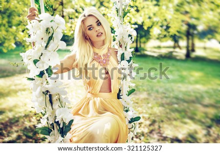 Perfect blonde beauty on flower swing - stock photo