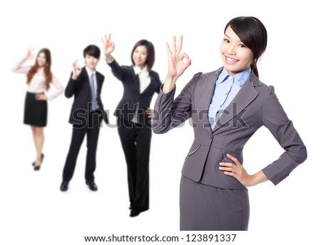 Perfect - business woman making the ok sign with her team behind. Young pretty Asian businesswoman isolated on white background. - stock photo