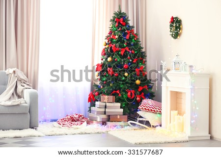 Perfect Christmas tree with gifts underneath in living room - stock photo