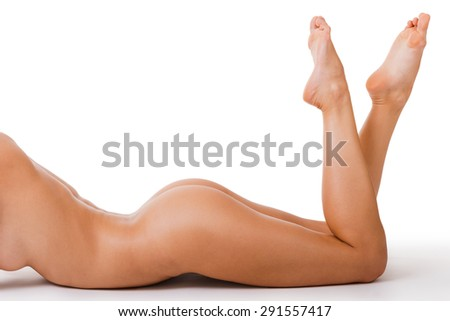 Perfect curves. Close-up of beautiful young naked woman with perfect body lying on her front and keeping feet up - stock photo