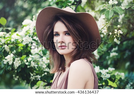 Perfect Face of a Beautiful Young Fashionable Woman in a Hat on Spring Blossom - stock photo