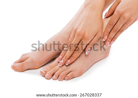 Perfect feet. Cropped picture of a beautiful young woman touching legs while sitting against white background   - stock photo