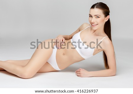 Perfect female legs on grey background - stock photo