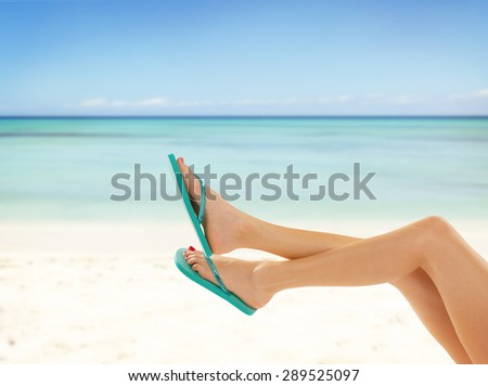 Perfect female legs on sandy beach with sandals - stock photo