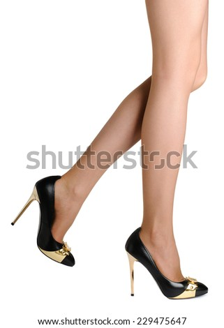 Perfect female legs wearing black high heel shoes  isolated on white background.  - stock photo