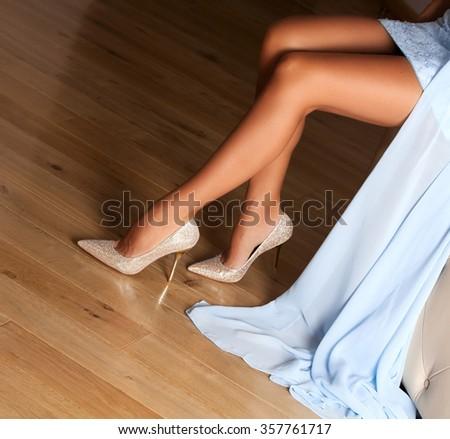 Perfect female legs wearing high heels. - stock photo