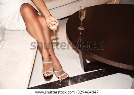 Perfect female legs wearing high heels. Woman drinking champagne. Holidays and relaxation concept - stock photo