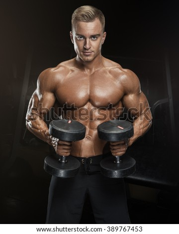 Perfect fit athletic guy workout with dumbbells, perfect abs, shoulders, biceps, triceps and chest. Fitness muscular body isolated on dark background. - stock photo