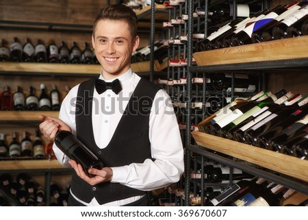 Perfect for your dinner. Young cheerful sommelier holding a bottle of wine smiling to the camera at the wine cellar - stock photo