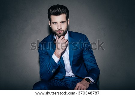 Perfect handsome. Young handsome man in suit and bow tie looking at camera and holding hand on chin while sitting against grey background - stock photo