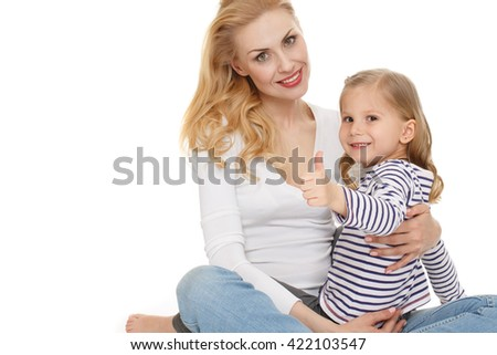 Perfect! Horizontal shot of a beautiful adult woman and her little daughter looking to the camera smiling showing thumbs up on white background. - stock photo